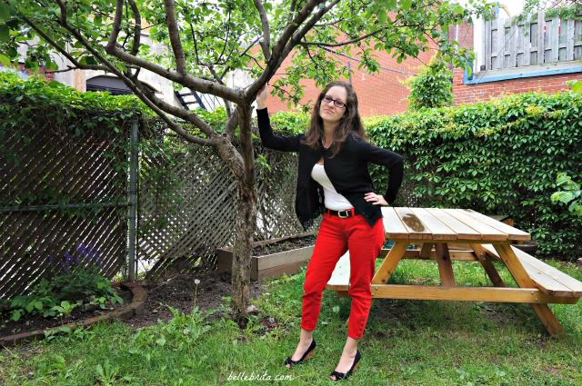 Sweet and sassy in a black cardigan, white tee, and red ankle jeans.