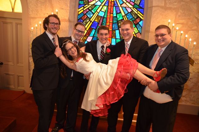 A playful wedding shot with the bride, groom, and their brothers.