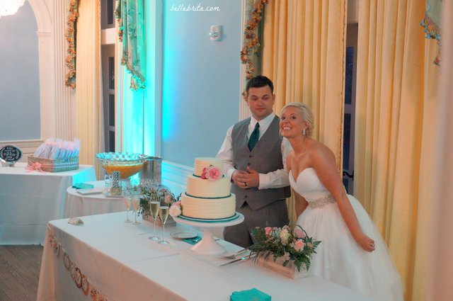The bride cheeses for a photo before cutting the wedding cake with her new groom | Belle Brita