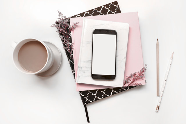 Coffee cup, smart phone, notebooks, pink desk flat lay.