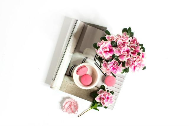 Pink flowers, pink macarons, magazine flat lay