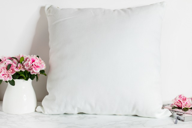 White vase, pink flowers, white pillows