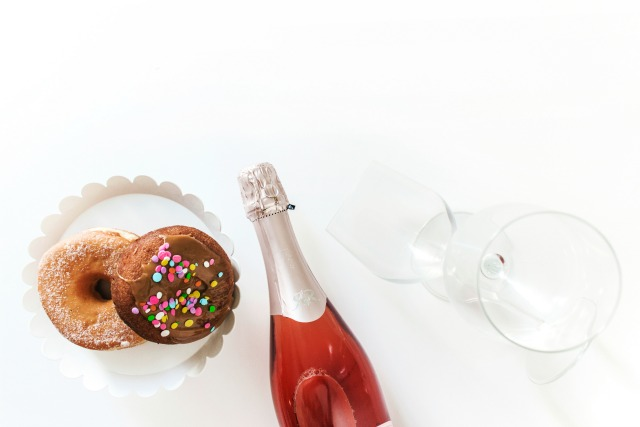 Donuts, blush sparkling wine, wine glasses flat lay