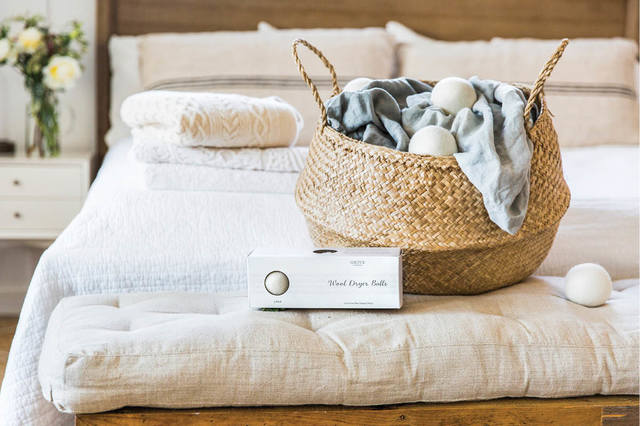 Laundry basket on bed, wool dryer balls