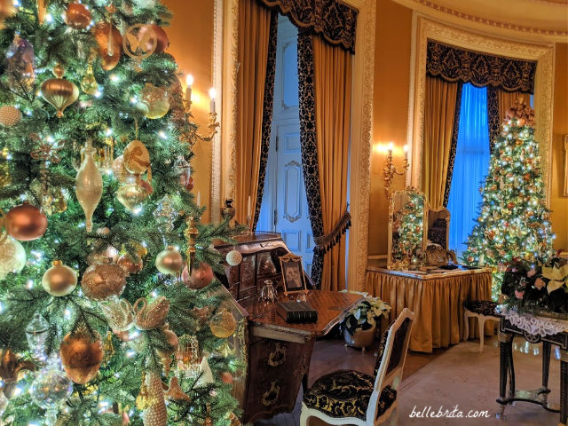 A bedroom decorated in gold, with a large Christmas tree on the left, another Christmas tree on the right, and a reflection of a tree in a vanity mirror