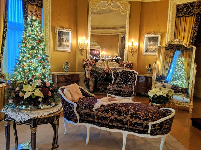 A bedroom decorated in gold, with purple furnishings. A Christmas tree on the left, and a Christmas tree reflected in a mirror on the right.