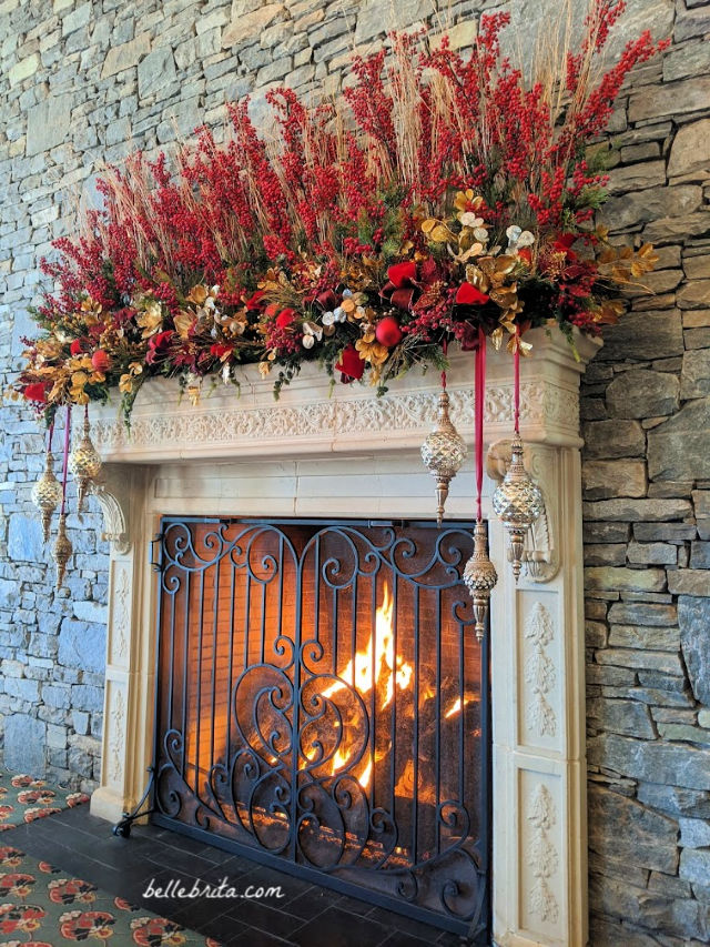 Large lit fireplace with the mantle decorated for Christmas