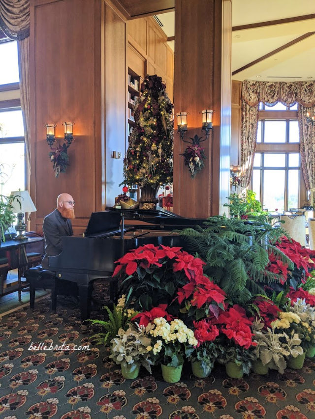 Man playing a grand piano, surrounded by Christmas decorations and fresh flowers