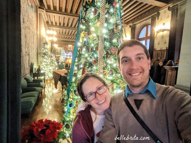 Woman and man smiling, standing in front of a row of Christmas trees at Biltmore