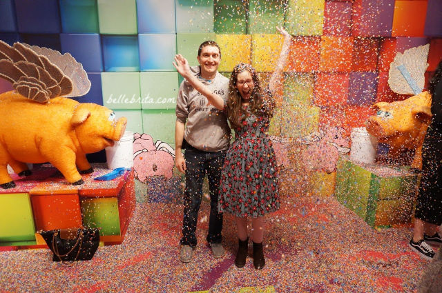 White man and white woman in a colorful room with confetti