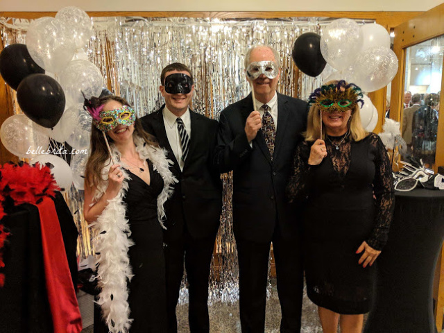 Four white people dressed up, wearing masks