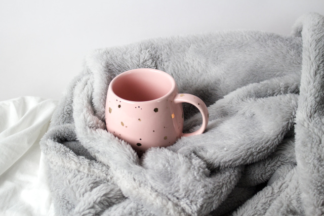 Pink and gold mug, gray blanket