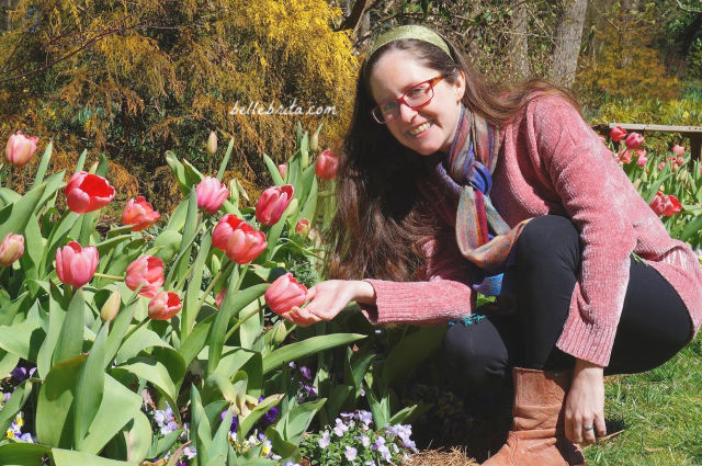 White woman wearing a pink Marley Lilly sweater and black leggings, crouched near pink tulips.