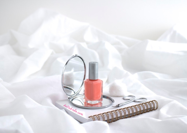 Coral nail polish, white notebook, beauty supplies, white blanket.