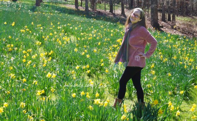 White woman wearing pink Marley Lily sweater and black Pact leggings standing in a field of daffodils.