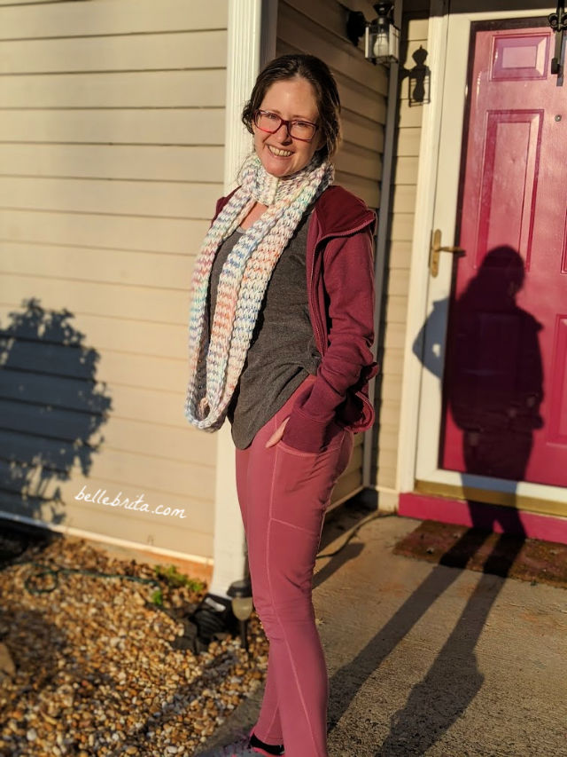 White woman wearing pink Pact leggings, standing in front of a pink door.