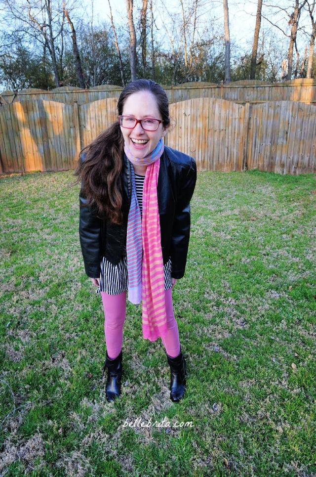 White woman laughing, wearing pink Pact leggings, standing in green yard.