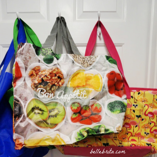 Colorful reusable grocery bags hanging on a door, another of my favorite one-use plastic alternatives