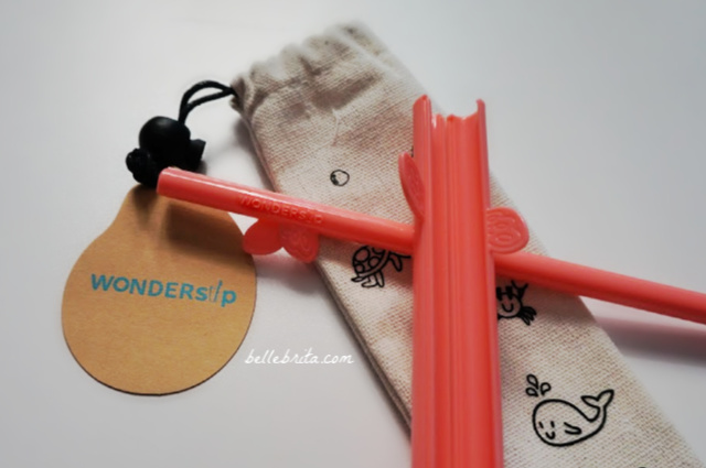 Reusable coral WonderSip Straws on a white table
