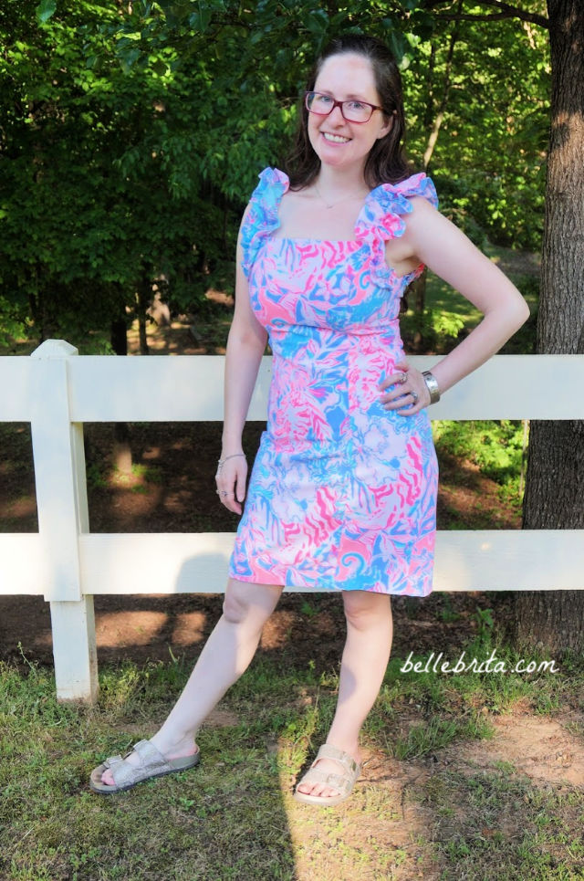 White woman wearing a pink, white, and blue Lilly Pulitzer sundress