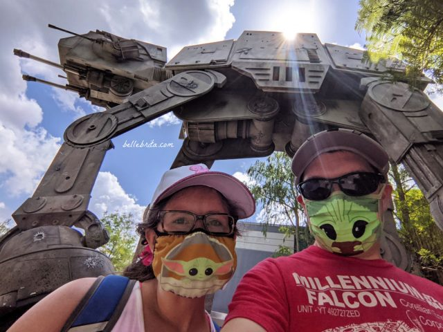 White man and white woman wearing Baby Yoda face masks outside of Star Tours in Hollywood Studios