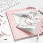 White keyboard, pink notebook, white note card, white mouse, desk flat lay