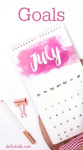 Flat lay of a July calendar and office supplies with a text overlay that reads Goals