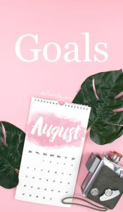 Pink flat lay with August calendar and green leaves. Text overlay reads Goals.