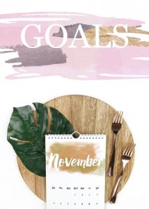 Flat lay with November calendar, wooden tray, green leaf, gold forks. Text overlay reads GOALS.