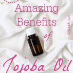 "Amber glass bottle on sheets. Text overlay reads: ""13 Amazing Benefits of Jojoba Oil"""